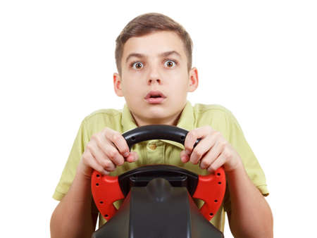 dream car: Teen Boy plays a driving game console with a surprised facial expression , isolated on white