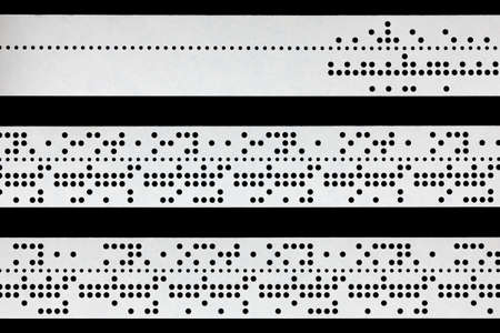 punched: Closeup of perforated punched tape, obsolete data storage, isolated on black background Stock Photo