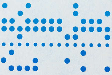 early 60s: Background macro of perforated punched tape, obsolete data storage on blue