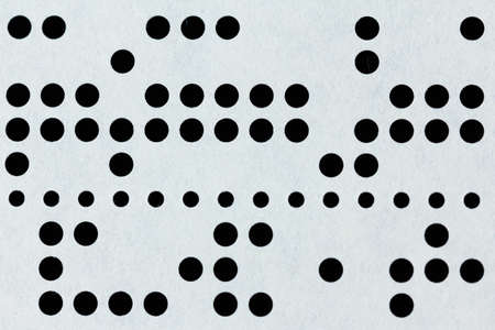 early 60s: Background macro of perforated punched tape, obsolete data storage on black