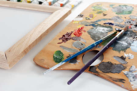oilpaint: Art palette with paint, border and a brush on white background