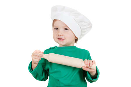 laughable: laughable little cook boy kneading the dough for the cookies, isolated on white background.  Half-length portrait of the table in studio