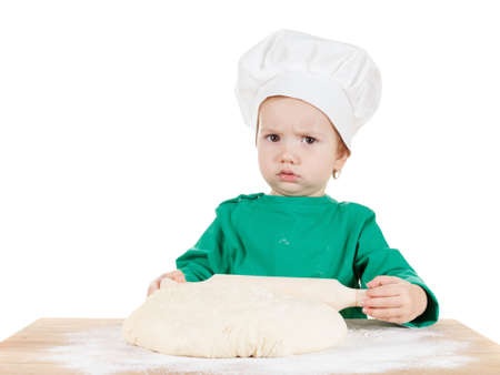 haciendo pan: Serious little cook boy kneading the dough for the cookies, isolated on white background.  Half-length portrait of the table in studio