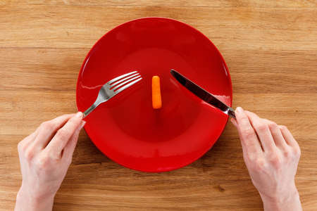 Concept of dieting, healthy eating properly. On wooden table is a plate with small carrot. Girls hands with fork and knife, preparing to eat