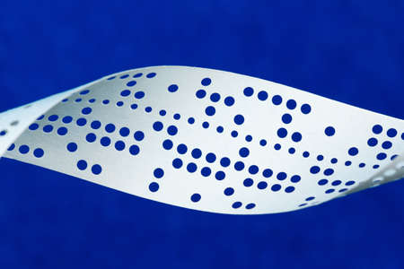 punched: Closeup of perforated punched tape, obsolete data storage, on blue background