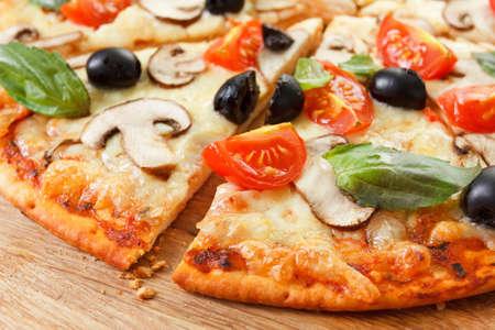 comida italiana: Pizza en rodajas con hongos, aceitunas y tomates. Albahaca, romero y verduras frescas. recientemente hecho en casa