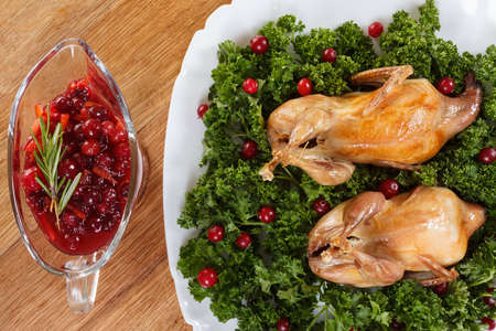 carcasses: Carcasses of quail roasted with sweet and sour cranberry sauce and parsley on a wooden table