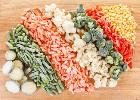 deep freeze: Mixed vegetables background. Deep Freeze for longer storage on a wooden table Stock Photo