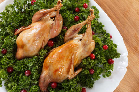 carcass meat: Carcasses of quail roasted with sweet and sour cranberry sauce and parsley on a wooden table