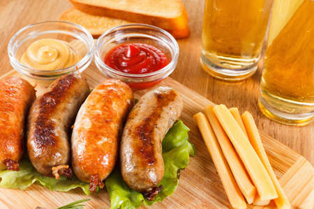 barbeque: Oktoberfest traditional menu, beer and roast beef or chicken sausage  with ketchup, mustard and rosemary. Wooden background