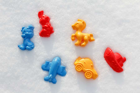 covered in snow: Overhead view on colorful toys, which are filled up with snow, covered snow,  on the white snow