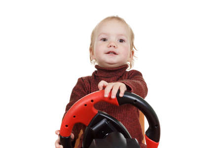 Infant with a happy expression on his face plays a driving game console, isolated on white Imagens