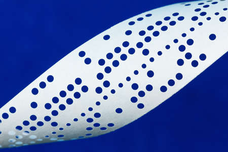 perforated: Closeup of perforated punched tape, obsolete data storage, on blue background