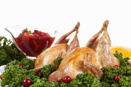 carcasses: Carcasses of quail roasted with sweet and sour cranberry sauce and parsley on white background