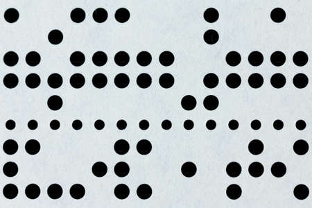 punched: Background macro of perforated punched tape, obsolete data storage on black