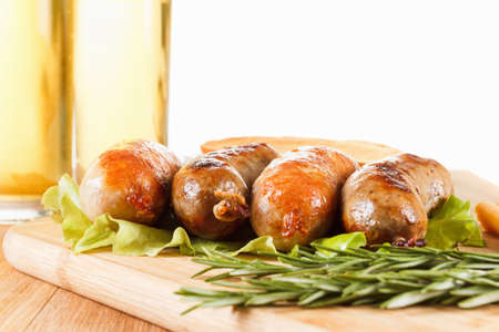 alehouse: Oktoberfest traditional menu, beer and roast beef or chicken sausage  with ketchup, mustard and rosemary. Wooden background