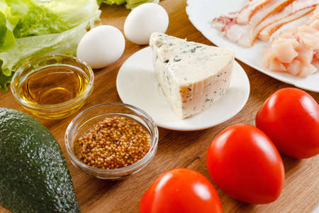 entree: Ingredients for cooking Traditional American Cobb Salad - Colorful entree  salad with bacon, chicken, eggs and tomatoes a main-dish American salad