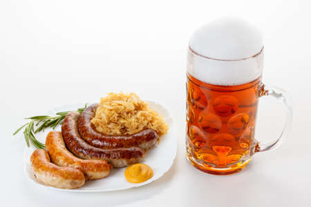 bier festival: Octoberfest menu, beer mug with foam, a plate of sausages and sauerkraut. Oktoberfest meal.