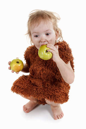 neanderthal: Little funny Neanderthal boy in a suit with a dirty face eating an apple. Humorous concept ancient caveman. On white background. Stock Photo