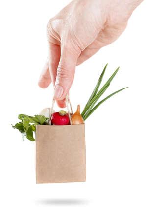 Un paquete de verduras establecidos en la mano. concepto de venta y entrega de productos. Aislado en blanco