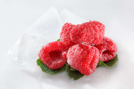 perishable: Frozen raspberries macro with mint leaves and ice  on white background Stock Photo