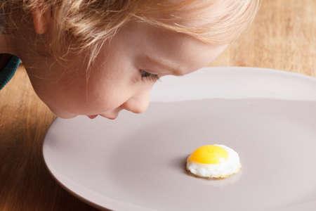 nutrientes: El niño caucásico que mira una pequeña tortilla de desayuno