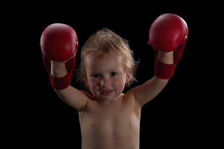 kickboxer: Boy athlete, boxer or kickboxer gloves training. Black background.