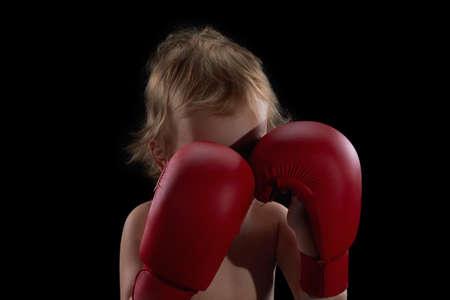 combative sport: Boy athlete, boxer or kickboxer gloves training. Black background.