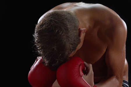 combative sport: Young boy athlete, boxer or kickboxer gloves after losing or training. Black background. Stock Photo