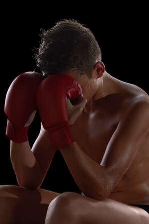 kickboxer: Young boy athlete, boxer or kickboxer gloves after losing or training. Black background. Stock Photo