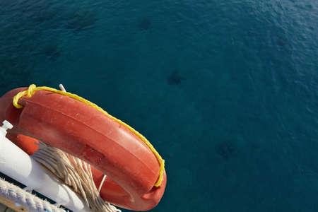 life preserver: Orange life preserver on a background of blue sea