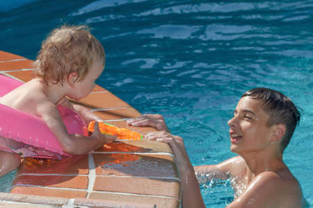 hermanos jugando: Two brothers playing in the pool on a summers day holiday