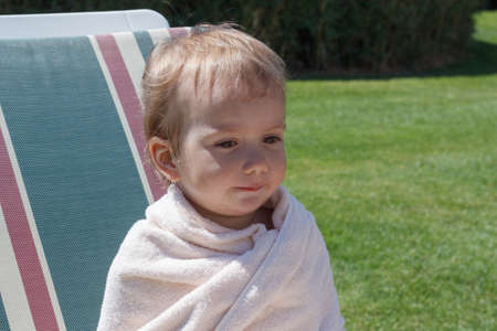 recliner: Happy boy wrapped in towel sitting on recliner of outdoor swimming pool