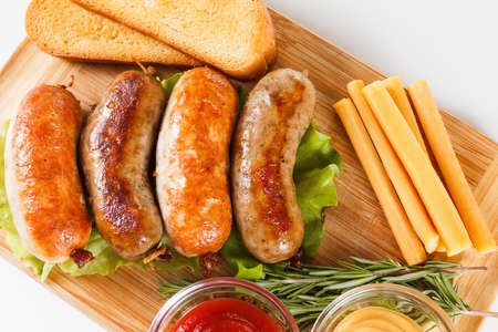 Oktoberfest traditional menu, beer and roast beef or chicken sausage  with ketchup, mustard and rosemary. Wooden background