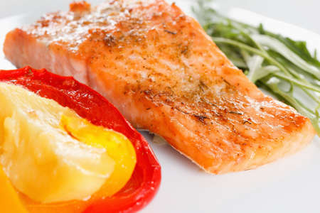 Baked prepared salmon fillet with vegetables, spices and arugula on a plate closeup