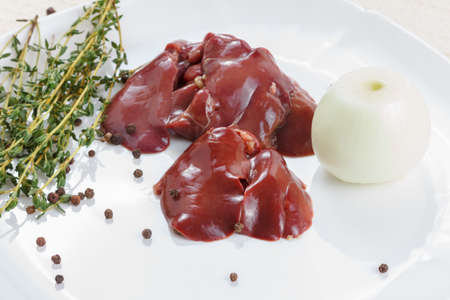 Fresh raw chicken liver with spices on white background. Cooking food.