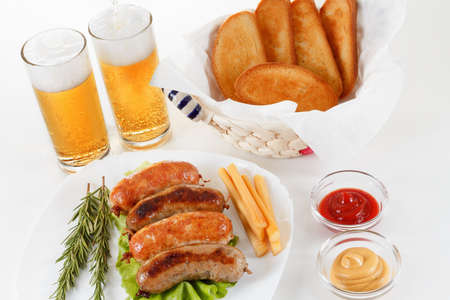 Oktoberfest traditional menu, roast beef or chicken sausage on a plate with ketchup, mustard and rosemary. White background