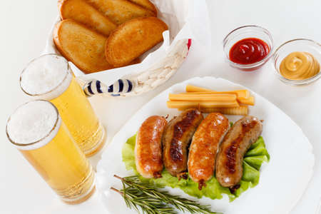 alehouse: Oktoberfest traditional menu, roast beef or chicken sausage on a plate with ketchup, mustard and rosemary. White background