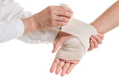 Doctor imposes an elastic compression bandage to the patients wrist with injury to the ligaments isolated on white