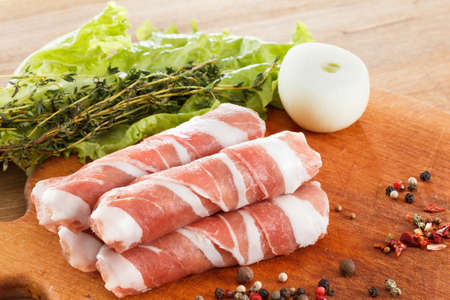 meaty: Slices of bacon roll closeup on cutting board with lettuce and spices, cooking food Stock Photo
