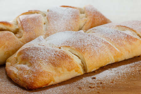 strewed: Ruddy roll is strewed by powdered sugar with a stuffing from apple jam