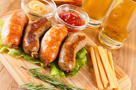 Oktoberfest beer traditional menu, grilled sausage with ketchup, mustard and rosemary. Wooden cutting board Stock Photo