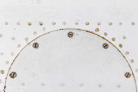 Old aluminum background detail of a military aircraft, surface corrosion. Oxidized metal texture with rivets. Stock Photo