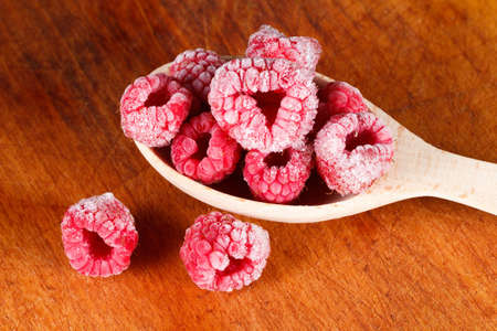 Several frozen raspberries in a wooden spoon closeup Stock Photo