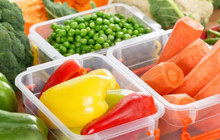 Trays with raw vegetables for freezing. Stocking up for winter storage in plastic containers