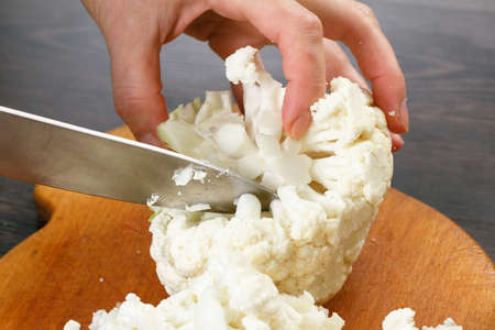 Stock up on winter food. Chef cutting cauliflower cooking. Imagens