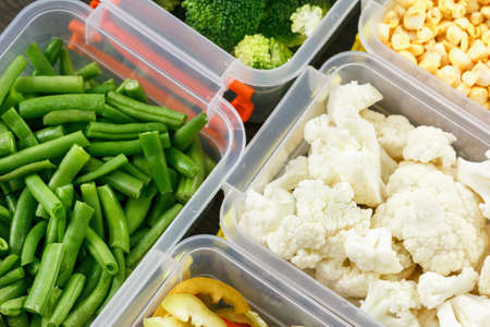 Trays with raw vegetables for freezing. Stocking up for winter storage in plastic containers. Overhead view.