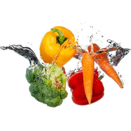 Vegetables thrown into a water. Splashes and drops