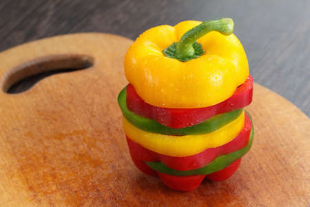 splitting: Dieting concept. Fresh sliced bell peppers on wooden cutting board Stock Photo