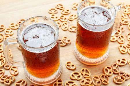 german alcohol: Mug of foamy beer alcohol with german pretzel. Traditional bavarian Oktoberfest snacks and drink in bar on wooden background